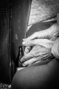 A homeless man's hands pictured near a discreetly hidden beer bottle.